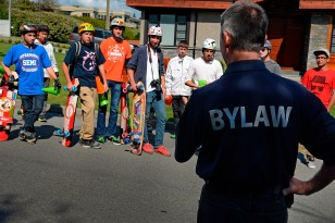 Dan Pape, centre, and a group of longboarders, were stopped from longboarding in White Rock Friday by bylaw and RCMP officers. Pape said the city needs to get moving on allowing the activity in order to endorse safety education in the community.