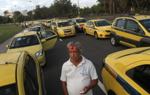APTOPIX - A cab driver wearing a red clown nose on his head, stands amid taxi cars during a protest by drivers against the Uber ride sharing service, in Rio de Janeiro, Brazil, Friday, July 24, 2015. Cab drivers complain that Uber represents unfair competition because its drivers and their cars are not submitted to regular inspections by city officials nor pay any kind of fees to the city to exercise their profession. Some protesters wore clown noses, so as to say Uber is making clowns of them. (AP Photo/Luiz Lopes)